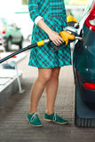 Woman fills petrol into her car at a gas station Stock Photo