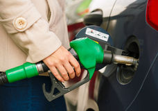 Woman fills petrol into her car at a gas station. Closeup royalty free stock photography
