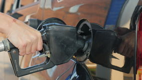 A woman fills petrol your car. In the frame are only visible hands and opening the gas tank stock video