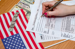 Woman fills the tax form 1040 with money, pen, flag of USA and calculator stock photo