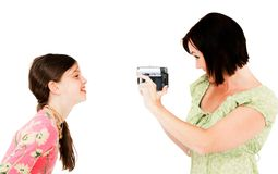 Woman filming girl. Woman filming a girl with a home video camera isolated over white Royalty Free Stock Photo