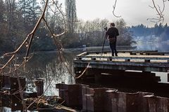 Woman filming on old dock. Photographer on fishing dock shoots along winter lake Stock Photography