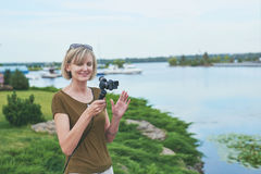 Woman filming with small personal camera Stock Images