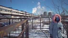 A woman in a filtering mask walks over a bridge next to large-diameter pipes. A young woman in a protective mask and gray park goes over the bridge against the stock footage