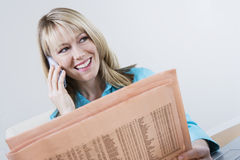 Woman With Finance Newspaper On Call Royalty Free Stock Images