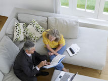 Woman With Financial Advisor On Sofa Stock Image