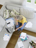 Woman With Financial Documents And Laptop Stock Photography