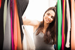 Woman finding something to wear. Cute young brunette trying to find something to wear in a closet at home Stock Photography
