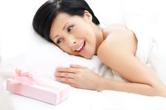 Woman finds a gift in bed Royalty Free Stock Photo