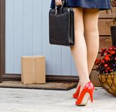 Woman finds parcel delivery at front door. Woman arrives home after work with briefcase to find a delivery parcel at door royalty free stock image