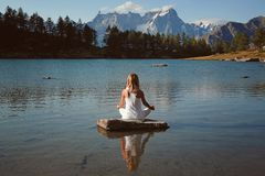 Woman finds peace in mountain lake. Yoga position royalty free stock images