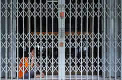 A woman finds privacy behind folding gate. BANGKOK, THAILAND - MAY 06, 2018: A woman finds some privacy and uses her mobile phone behind a retractable mettalic royalty free stock photography