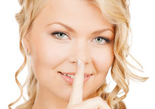 Woman with finger on her lips. Business, communication concept - picture of mysterious woman with finger on her lips royalty free stock images