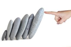 Woman finger hold stones. Woman finger stops stones from tumble down Royalty Free Stock Image