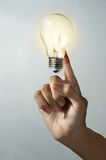 Woman finger with light bulb. Royalty Free Stock Photography