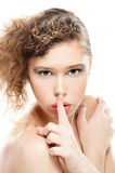 Woman with a finger on lips Stock Images