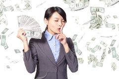 Woman finger on lips asking quiet with money. Business woman finger on her lips asking quiet with falling money isolated on white background, asian model Stock Image