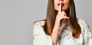 Woman with finger on lips stock photography