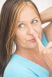 Woman with finger on lips and nose Stock Images