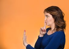 Woman with finger on lips, shhh gesture asking be quiet. Closeup side view profile portrait serious woman finger, hand on lips, shhh gesture asking be quiet Royalty Free Stock Image