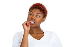 Woman with finger in mouth, sucking thumb, biting fingernail in stress