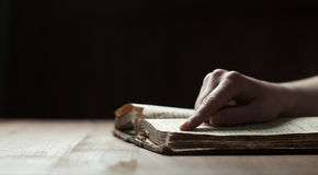 Woman finger presses on old bible book Royalty Free Stock Image