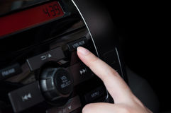 Woman finger pressing button USB AUX detail on a car`s dashboard Stock Images