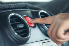 Woman finger pressing emergency button on car dashboard. In vintage color tone Stock Photos