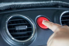 Woman finger pressing emergency button on car dashboard. In vintage color tone Stock Photo