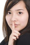 Woman with finger to lips Stock Images