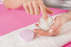 Woman finger touching open cream for hands on white towel royalty free stock image