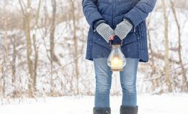 Woman standing outside holding lantern while snow is falling. Woman in fingerless gloves standing oute holding lantern while snow is falling Stock Photos