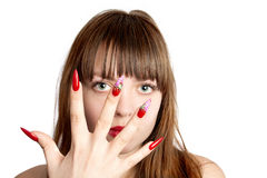 Woman with fingernails. Beautiful young woman with long red nails, over her face, over white background stock image