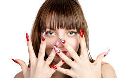 Woman with fingernails. Beautiful young woman with long red nails, over her face, over white background stock photos