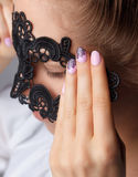 Woman fingers with beautiful romantic nails. Woman holding a lacy mask with matching romantic fingers stock image