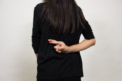 Woman fingers crossed on his back. The women crossed  fingers behind  back, isolated on white Stock Image