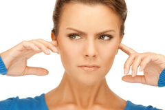 Woman with fingers in ears. Picture of woman with fingers in ears Stock Photography