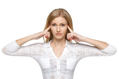 Woman with fingers in ears. Over white background Stock Image