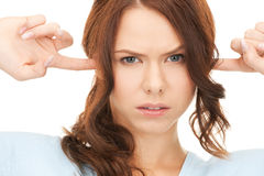 Woman with fingers in ears Stock Photos