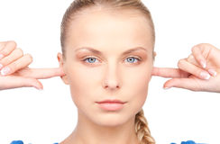Woman with fingers in ears Stock Image