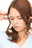 Woman with fingers in ears. Picture of woman with fingers in ears Stock Images