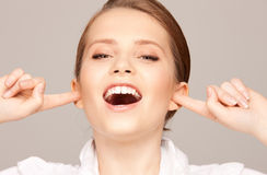 Woman with fingers in ears. Picture of woman with fingers in ears Royalty Free Stock Images