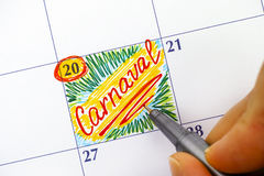 Woman fingers with pen writing reminder Carnaval in calendar Stock Image