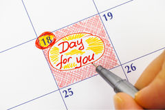 Woman fingers with pen writing reminder Day for You in calendar. Royalty Free Stock Image