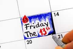 Woman fingers with pen writing reminder Friday The 13th in calen. Dar. Close-up stock illustration