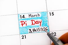 Woman fingers with pen writing reminder Pi Day in calendar. Pi Day is celebrated on March 14th 3/14 around the world stock photo