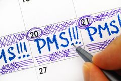 Woman fingers with pen writing reminder PMS in calendar. Close-up stock photo
