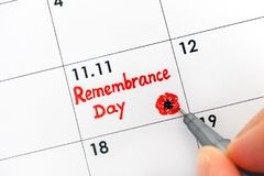 Woman fingers with pen writing reminder Remembrance Day in calen. Dar. Close-up royalty free stock image