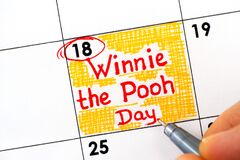 Woman fingers with pen writing reminder Winnie the Pooh Day in calendar