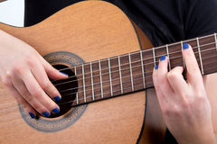 Woman fingers playing guitar Stock Images